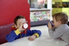 喝汁液的两个兄弟 图库摄影