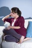 喝沉思沙发认为的妇女的咖啡 免版税库存照片
