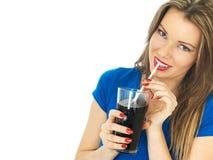 喝泡沫腾涌的可乐饮料的少妇 免版税图库摄影