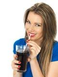 喝泡沫腾涌的可乐饮料的少妇 免版税库存图片