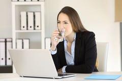 喝淡水的女实业家在办公室 免版税库存图片