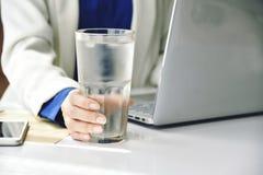 喝淡水的女商人,当工作在办公室,饮用水A杯在办公桌上时的 免版税库存图片