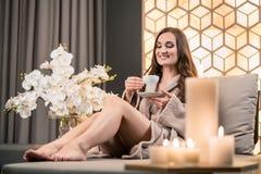 喝清凉茶的轻松的少妇在温泉治疗前 免版税库存图片