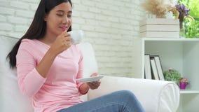 喝温暖的咖啡或茶的快乐的亚裔少妇享用它,当在家时坐在她的客厅 股票视频
