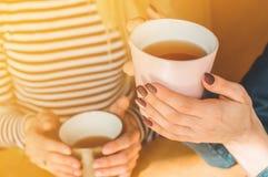 喝温暖的咖啡或茶的快乐的年轻女人享用它,当坐在咖啡馆时 免版税库存图片