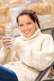 喝热可可粉松弛庭院的微笑的妇女 免版税库存照片