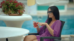 喝热带鸡尾酒的年轻时髦的美丽的妇女在手段水池附近 股票录像