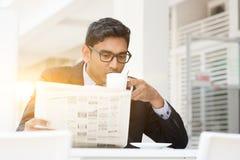 喝热的咖啡和读报纸的商人在caf 免版税库存图片