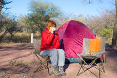 喝热的咖啡杯的妇女,当放松在露营地时 帐篷、椅子和露营齿轮 室外活动在夏天 偶然 库存图片