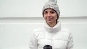 喝热的咖啡的女孩的面孔户外在被编织的手套和帽子愉快微笑的冬天 股票录像