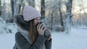 喝热的茶或咖啡从欢乐杯子的女孩有多雪的公园的 股票视频