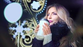 喝热的茶或咖啡的妇女在圣诞装饰背景 股票录像