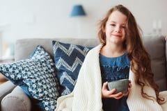 喝热的茶的儿童女孩从流感恢复 库存照片