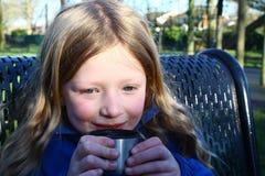 喝热的茶的冷的女孩 免版税库存照片