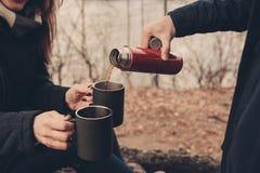 喝热的茶的夫妇生活方式捕获室外在舒适在森林里温暖步行 免版税库存照片