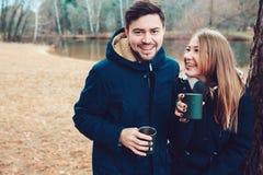 喝热的茶的夫妇生活方式捕获室外在舒适在森林里温暖步行 免版税图库摄影