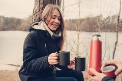 喝热的茶的夫妇生活方式捕获室外在舒适在森林里温暖步行 免版税库存图片