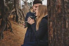 喝热的茶的愉快的夫妇生活方式捕获室外在舒适温暖步行 免版税库存图片