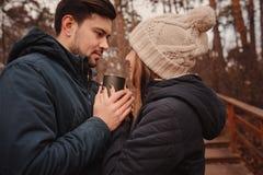 喝热的茶的愉快的夫妇生活方式捕获室外在舒适温暖步行 免版税库存照片