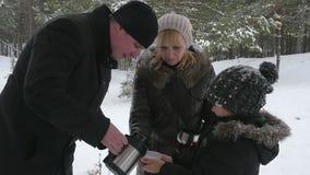 喝热的茶的愉快的家庭外面在冬天 股票录像