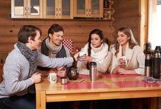 喝热的茶的最好的朋友在舒适厨房里在冬天村庄 库存照片