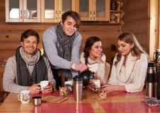 喝热的茶的最好的朋友在舒适厨房里在冬天村庄 库存图片