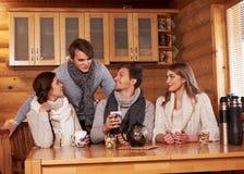 喝热的茶的最好的朋友在舒适厨房里在冬天村庄 免版税图库摄影