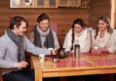 喝热的茶的最好的朋友在舒适厨房里在冬天村庄 免版税库存照片