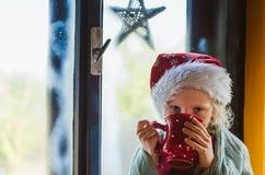 喝热的茶的逗人喜爱的女孩由窗口 图库摄影