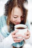 喝热的饮料的女性户外在冬天 免版税库存图片
