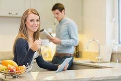 喝热的饮料的妇女使用片剂个人计算机在厨房里 库存照片