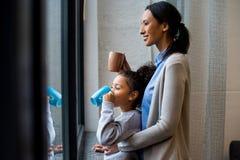 喝热的饮料的母亲和女儿 库存图片
