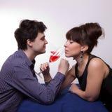 喝玫瑰酒红色年轻人的夫妇 库存照片