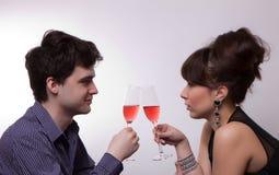 喝玫瑰酒红色年轻人的夫妇 库存图片