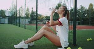 喝瓶网球场的水逗人喜爱的夫人外面,下来坐地板,好日子 影视素材