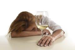 喝白葡萄酒玻璃绝望的白种人白肤金发的被浪费的和沮丧的醺酒的妇女被喝 免版税库存照片