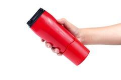 喝的水瓶在手上,在一白色backgrou 图库摄影