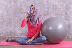 喝矿泉水的美丽的健康妇女在做瑜伽以后 免版税图库摄影