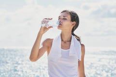 喝矿泉水的运动的妇女在锻炼以后 免版税库存照片