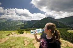 喝矿泉水的白种人少妇 免版税图库摄影