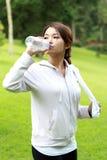 喝矿泉水的运动的妇女 免版税图库摄影
