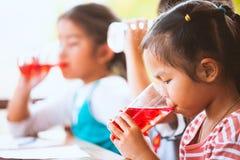 喝红色汁液的小组亚裔孩子浇灌与冰 免版税库存图片