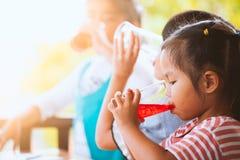喝红色汁液的小组亚裔孩子浇灌与冰 图库摄影