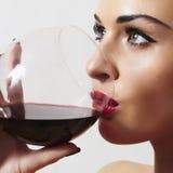 喝红色wine.make-up.red嘴唇的美丽的白肤金发的妇女 免版税库存照片