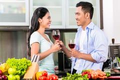 喝红葡萄酒的亚洲夫妇在厨房里 库存图片