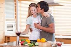 喝红葡萄酒的可爱的夫妇,当亲吻时 免版税图库摄影
