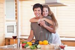 喝红葡萄酒的可爱的夫妇,当拥抱时 免版税库存照片