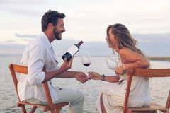 喝红葡萄酒的妇女和人在海边 免版税库存图片