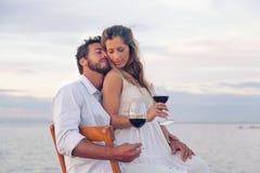 喝红葡萄酒的妇女和人在海边 免版税库存照片