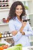 喝红葡萄酒的妇女在家庭厨房里 免版税图库摄影